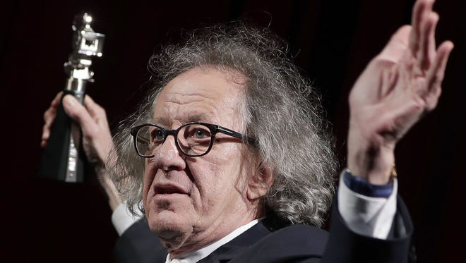 In this Feb. 11, 2017 file photo, Australian actor Geoffrey Rush poses with his 'Berlinale Camera Award' which he received prior to the screening of the film 'Final Portrait' at the 2017 Berlinale Film Festival in Berlin, Germany.