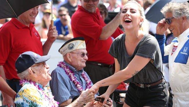 Singer and actress Lady Gaga talks with veterans of Pearl Harbor prior to the start of the 100th Indianapolis 500.