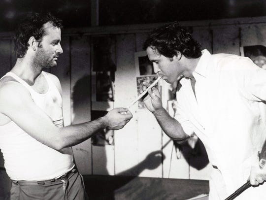 "Carl (Bill Murray) lights a ""big Bob Marley joint"" for Ty (Chevy Chase) in a scene from ""Caddyshack."""