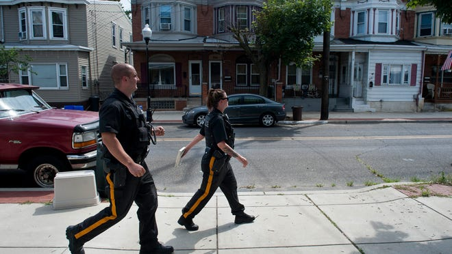 Gloucester City patrol officers  Keith O'Donnell and  Barbara Kane  walk a beat through a city neighborhood  Wednesday. The officers are part of the force's recently formed  Directed Patrol Unit, which uses high-visibility foot and bicycle patrols aimed at addressing quality-of-life issues as well as more serious crimes.