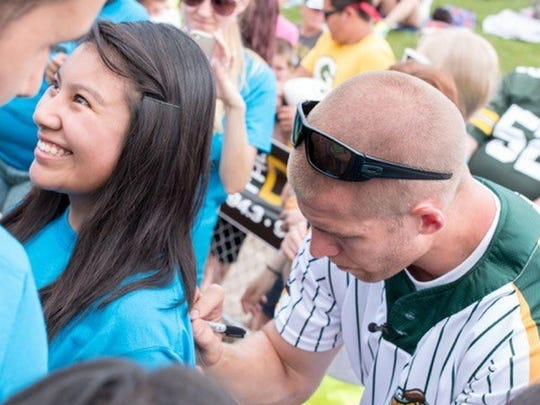 Green Bay Packers receiver Jordy Nelson, right, signs the shirt of Young Life Green Bay volunteer Jenny Perez at the second annual Jordy Nelson Charity Softball Game at Fox Cities Stadium in Grand Chute on Sunday. Nelson presented a $100,000 check to Young Life Green Bay, a nondenominational Christian ministry that supports adolescents.