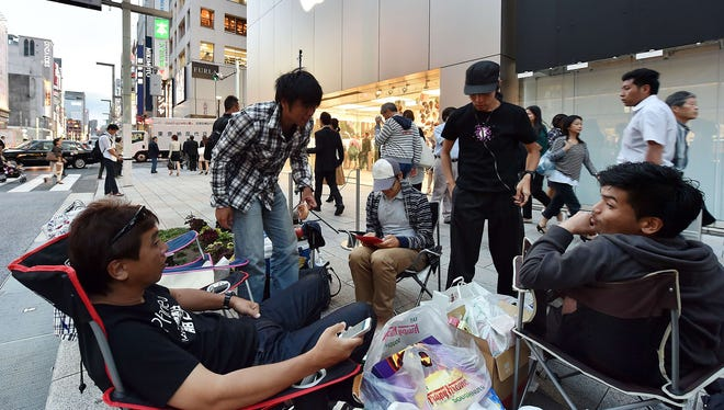 People wait in line outside of an Apple store on Sept. 18, 2014, in Tokyo.