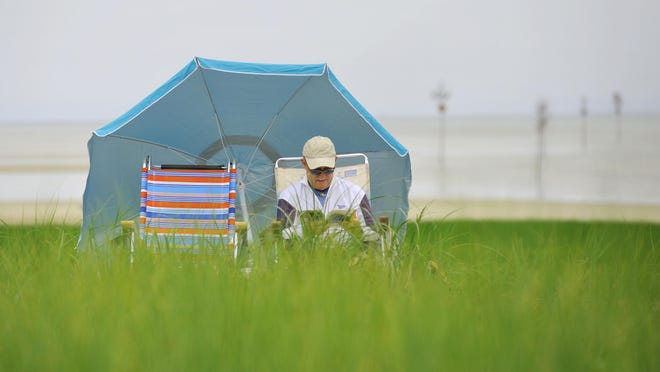 Jim Craig catches up on his summer reading last year waiting for the sun to burn through the clouds on a low mid-day tide at Rock Harbor. Today, he would be perfectly situated to enjoy outdoor reading while still socially distancing.