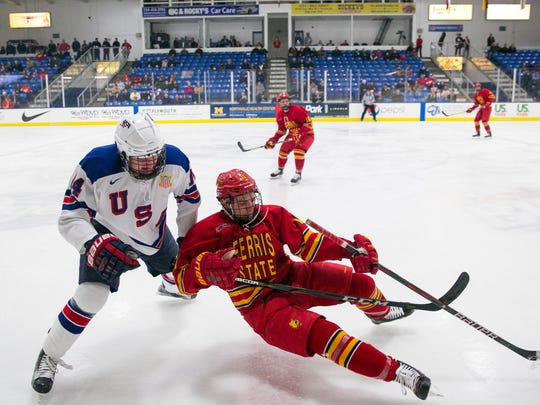 Jack DeBoer (14) of the U.S. NTDP Under-18 team checks Ferris State's Dominic Lutz (11) into the boards. Lutz is a Livonia Stevenson alum.