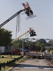 Several cranes with soft boxes and lighting gear are raised over a track in preparation for the filming of a car racing reality show at Eastman Business Park.