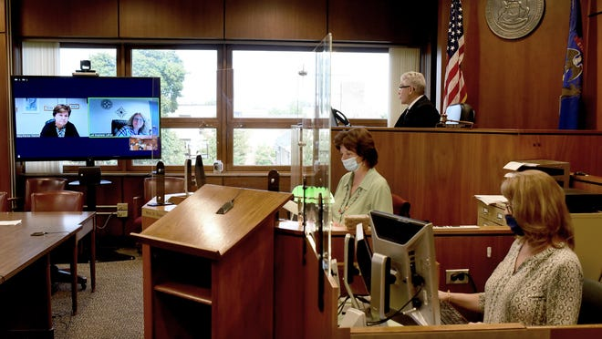 Monroe County 38th Circuit Court Judge Mark S. Braunlich conducts Zoom proceedings with Friend of the Court Director Mary Patrice-Patrick and assistant Stephanie LaPrad. Branlich's Clerk Nancy Frazee and court reporter Sarah Blanchett also are pictured.