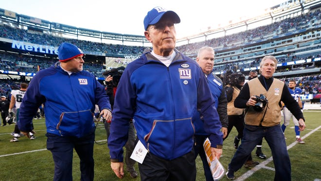 New York Giants head coach Tom Coughlin walks off the field after losing 35-30 against the Philadelphia Eagles . Coughlin stepped down on Monday.
