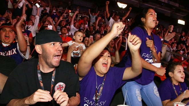 Suns fans Gerry Chaffin (left) and Andrew Chaffin (middle) react to Phoenix selecting Kansas guard/forward Josh Jackson with their first round pick during the NBA Draft on Jun. 22, 2017 at at Talking Stick Resort Arena in Phoenix, Ariz.