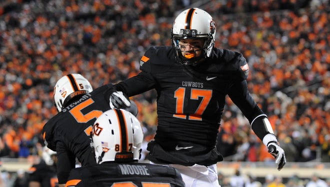Oklahoma State wide receiver Charlie Moore (17) celebrates a touchdown with teammate Josh Stewart (5) at Boone Pickens Stadium on Saturday.