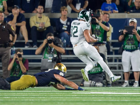 Michigan State Spartans wide receiver R.J. Shelton (12) runs for a touchdown as Notre Dame Fighting Irish safety Drue Tranquill (23) defends in the second quarter at Notre Dame Stadium.