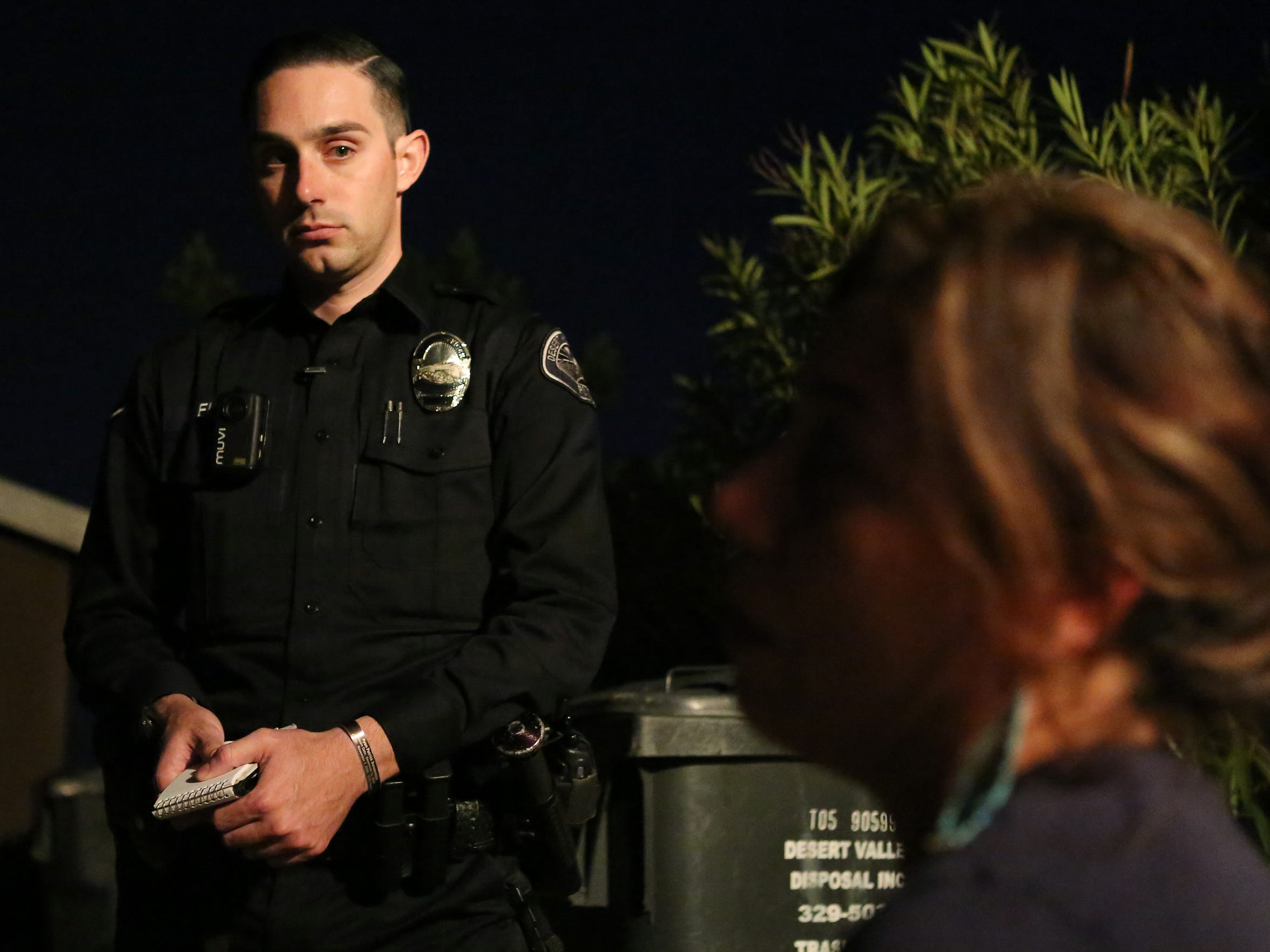 Desert Hot Springs officer Greg Elias listens as a woman reports that her husband attacked her in front of her children in Desert Hot Springs, Calif.