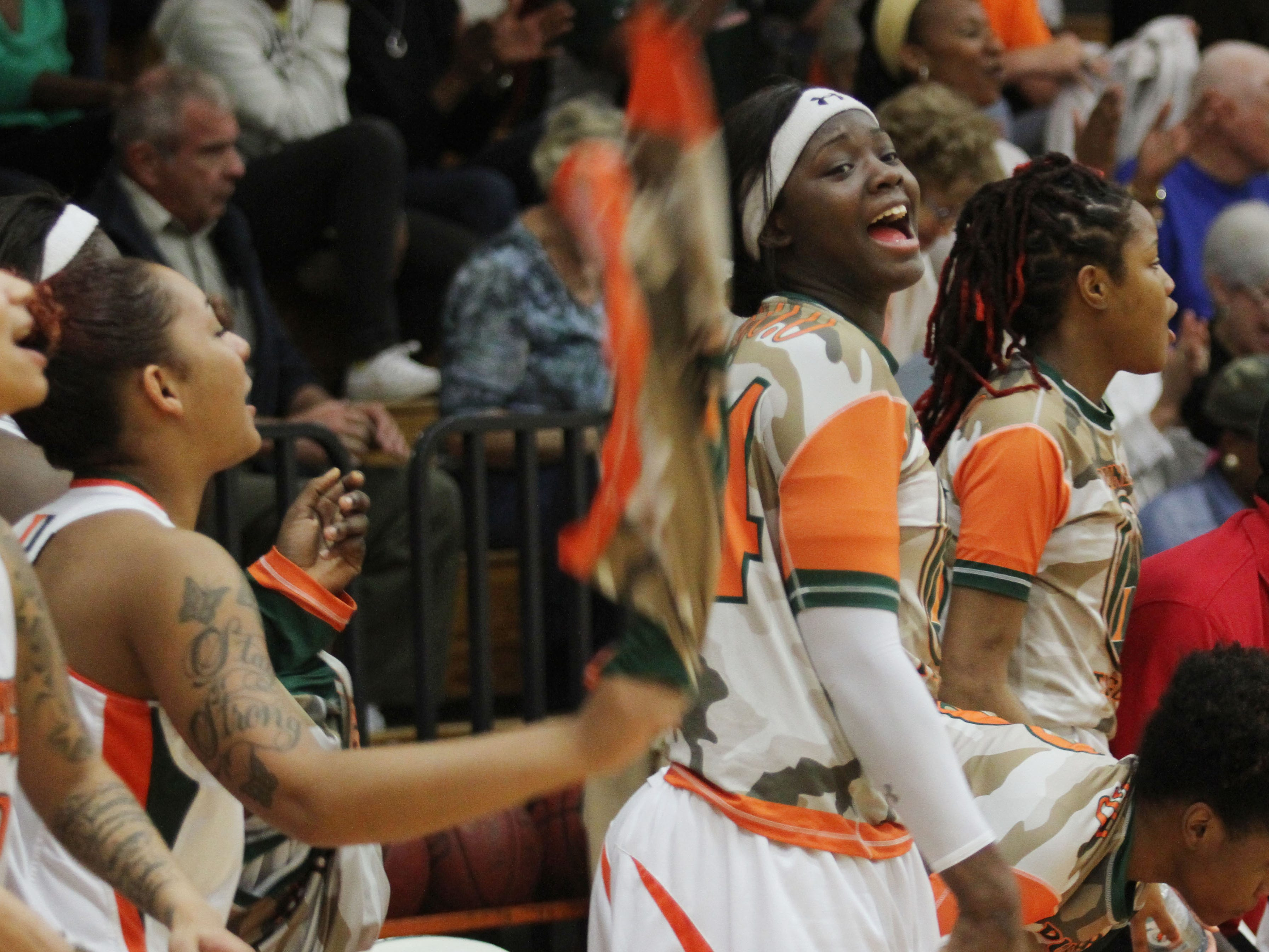Dunbar's Jamiah Bland, center, celebrates along with other Lady Tigers after defeating Tampa Catholic during the Region 4A-3 girls basketball championship game at Dunbar High School on Friday night.
