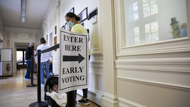 Voters line up with a limit of five people in the Easton Town Hall for early voting on Monday, Oct. 19, 2020. n.