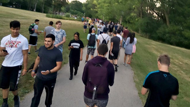 Throngs of people cross  Lake Park while playing Pokémon Go in July 2016, shortly after the release of the popular smartphone game.