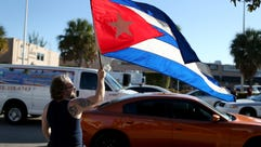 Abdel Rodriguez holds a Cuban flag as he stands outside