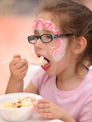 Delaney Kent takes a big taste of her ice cream sundae during the American Dairy Association's 25th annual Ice Cream Social in 2014.