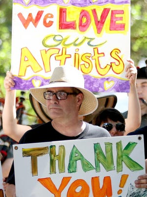 Don Hudgins, the Salem Art Association's new director of special events, carries signs during Sunday's closing ceremonies for the Salem Art Fair & Festival.