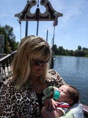 Tina Barnard holds her 25-day-old son, Josh, before leaving on his first river cruise on Wednesday, Aug. 5, 2015, in Salem, Ore.