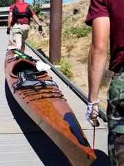Roland Mack, 55, and Alex Mack, 19, of Independence, carry Alex's handmade kayak out of the water Saturday at Wallace Marine Park in Salem after finishing first in the Great Willamette River Raft Race.