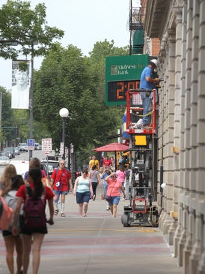 Pedestrians pass MidWestOne Bank on Clinton Street in Iowa City in this file photo from 2015.