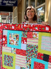Sylvia Dorney of Greenbaum's Quilted Forest holds one of the quilts created for the auction to benefit Fences for Fido.