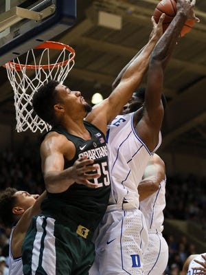 Michigan State forward Kenny Goins (25) and Duke forward Amile Jefferson (21) scramble for a rebound in the first half Tuesday in Durham, N.C.
