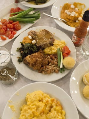 Fried chicken, pork chops, collard greens, macaroni and cheese, rice and beans, sweet potatoes and corn bread muffins cover each table Feb. 26, 2017, during the dinner series Sunday Nights at Grandma's at the Great Lakes Culinary Center in Southfield.