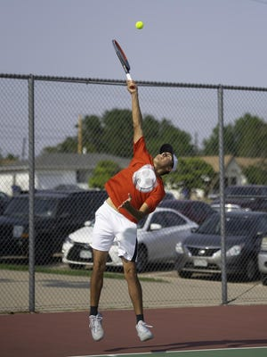Centennial High School's Zander Pacheco goes up high on a serve while taking on East's Ian Imes on Tuesday at the East High School courts.