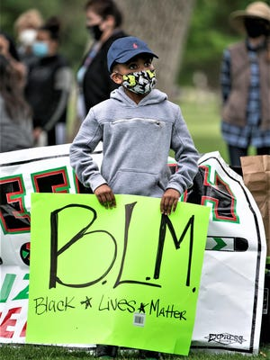 Bryson Sankey, 8, holds a sign in support of the Black Lives Matter movement during the Justice Rally and Juneteenth celebration at Mineral Palace Park Friday.