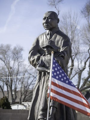 An American flag blows in the wind in front of a statue of Martin Luther King Jr. and Emmett Till during a commemoration ceremony last January honor King at the Friendly Harbor Community Center, 2713 N. Grand Ave.