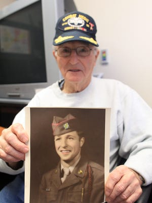 U.S. Army veteran John Gualtier, 89, of Vinton holds a photo of himself from World War II at the VA Outpatient Clinic in Coralville on Tuesday. He served as a medic in the war.