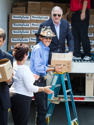 Representatives from Smithfield, Tops Friendly Markets, and the Food Bank of the Southern Tier line up beside Richard Petty to help unload a portion of the 40,000-pound protein donation from Smithfield's Helping Hungry Homes tour in this 2014 photo.