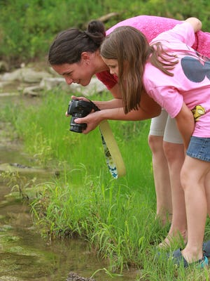 Lana Sovereign and her 10-year-old daughter, Sienna, of Windham, N.H., look for frogs Friday at the Devonian Fossil Gorge in Iowa City.