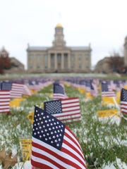 Flags are displayed in front of the Old Capitol Museum on Tuesday, Nov. 11, 2014.  David Scrivner / Iowa City Press-Citizen
