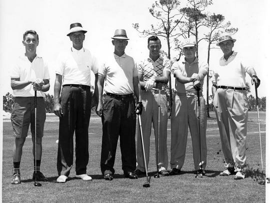Golf pro Ed Caldwell poses with unidentified golfers