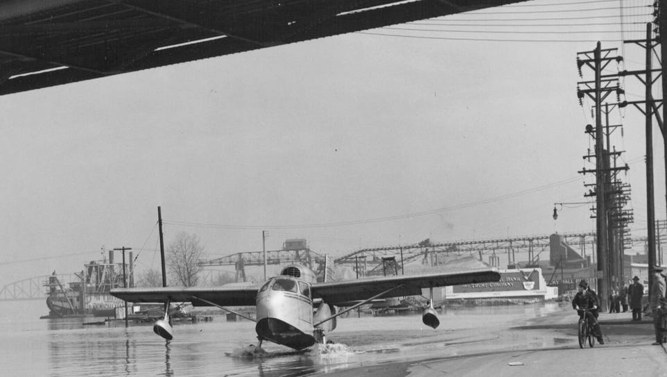 As flood waters rise in February 1950, a seaplane heads