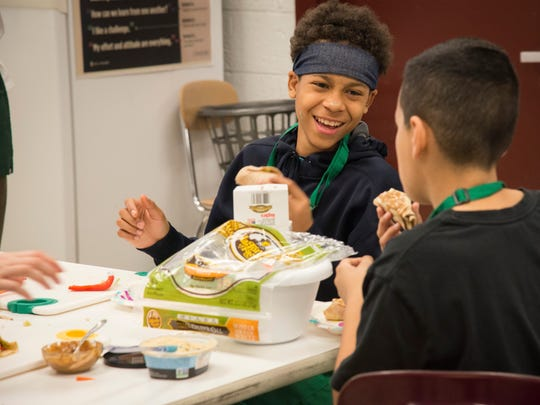 Owen Middle School student Malik Hill gets ready to launch into his veggie wrap at the Green Aprons Club recently.