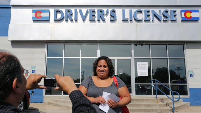 In this file photo, immigrant and longtime resident in the United States Rosalva Mireles is photographed by Jesus Sanchez of Spanish language newspaper El Commercio, after Mireles was processed for her permanent driver's license in Denver.