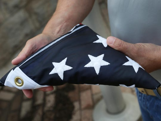 Steve Stiegelmeyer holds a folded American flag brought down from above the USS Indianapolis Memorial on the Canal Walk downtown, Tuesday, June 9, 2015. Through the Lost at Sea program, flags are being flown at the memorial daily for a different person. The flags are then given or sent to the family of the sailors. John Cadwallader is one of the sailors who died when the ship sank after being torpedoed. Of the 1,196 aboard, 900 made it into the water, but only 317 survived almost five days in the water through shark attacks, starvation, thirst, exposure and wounds. Cadwallader's family received this flag.