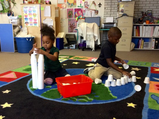 Ayana Cooks and Keyante Cherry, pre-K and kindergarten students in Jolie Sadler's class at Peabody Montessori Elementary School, build using 100 cups Monday as part of their 100th day of school celebration. Kids worked in pairs in centers completing activities with the 100-day theme.