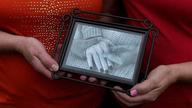 Sisters Judy Juengel, left, and Ruthann Bettcher hold a photo Sept. 29, 2015, of them holding their mother's hands. Viola Kogelman was recently part of a  program called Holding Hands Forever, where hospice workers photograph a loved one's hands before they die.