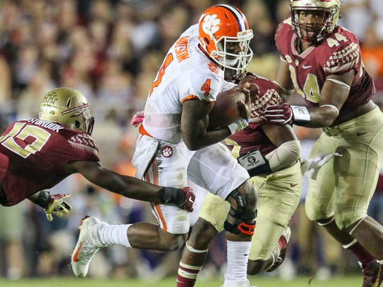 Clemson quarterback Deshaun Watson (4) runs by Florida State defensive back Lawrence Dawsey, Jr.(13), and defensive end DeMarcus Walker (44), right, during the second quarter on Saturday October 29 at Doak Campbell Stadium in Tallahassee, Florida.