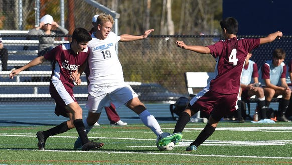 John Jay-East Fishkill's Matt Howe, center, tries to