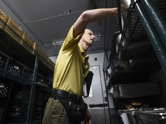 Larimer County health inspector Paul Rees checks food in a refrigerator in the kitchen of the Alternative Sentencing Facility in this file photo.