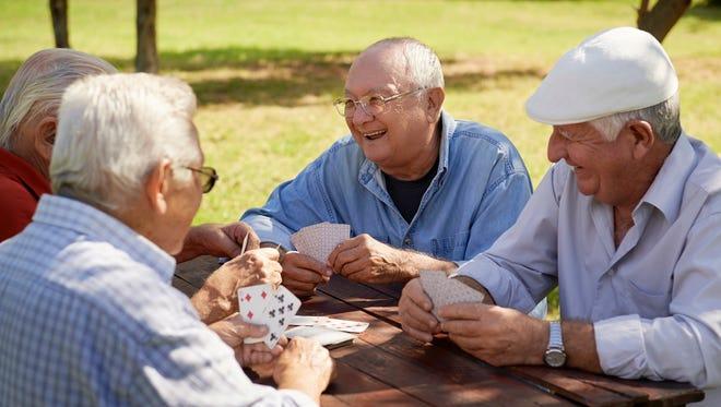 Senior men playing chess at park.
