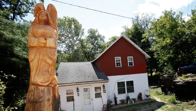 An angel has been carved from a maple tree that was damaged in April when a dump truck hit it and then a rock wall before spinning into a parked vehicle and nearly bouncing into a Big Flats home on state Route 352.