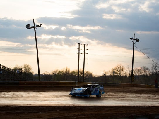 A late model car takes warm up laps around the new