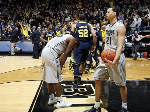 Feb 26, 2014; West Lafayette, IN, USA; Michigan Wolverines forward Glenn Robinson III  (1) are surrounded  by his teammates after making a shot at the buzzer to win the game as Purdue Boilermakers forward Rapheal Davis (35) and guard Kendall Stephens reacts at Mackey Arena. Michigan defeats Purdue 77-76. Mandatory Credit: Brian Spurlock-USA TODAY Sports