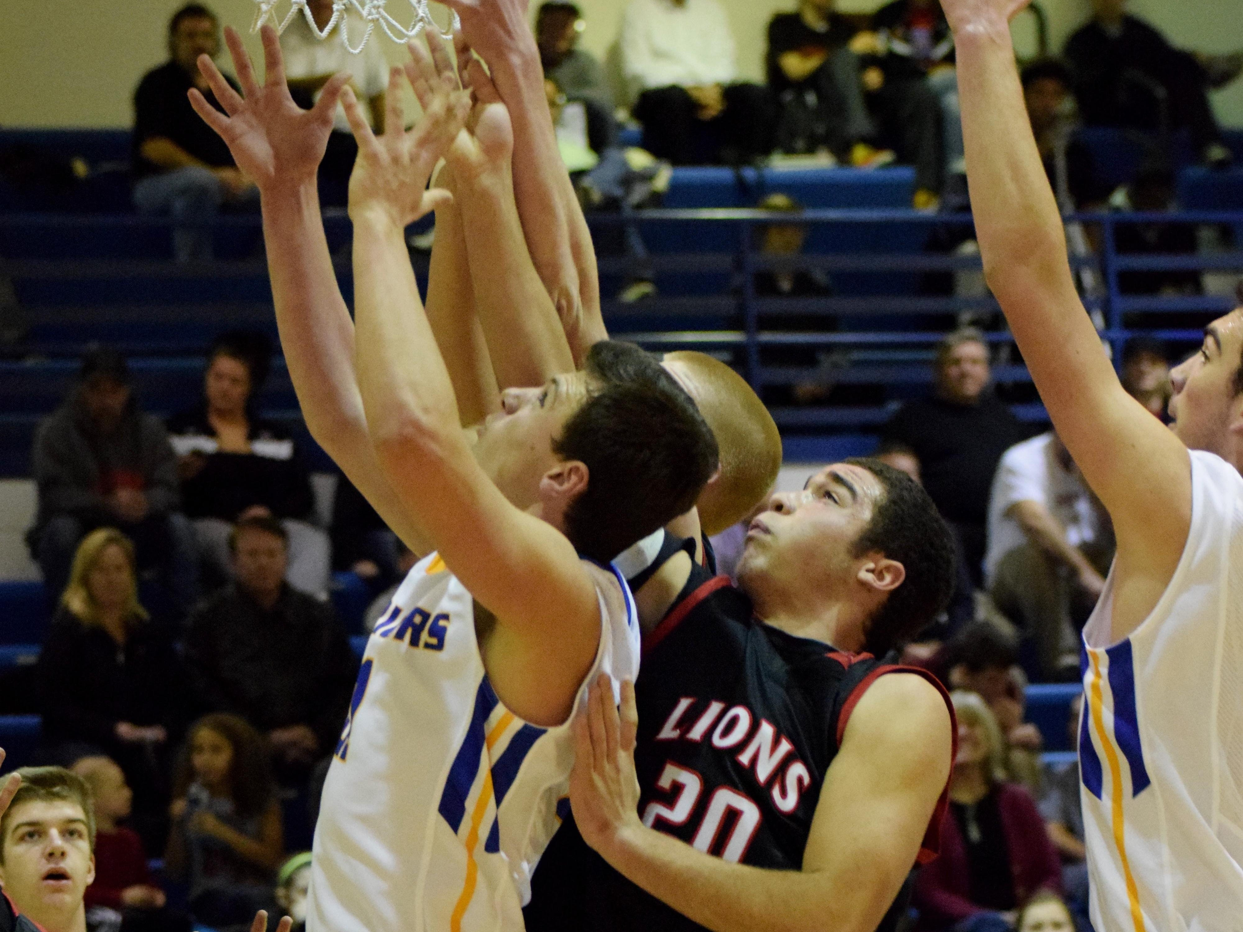 Mariemont's Brennan Crowley, front, fights for a rebound against New Richmond's Isiah Young (20).