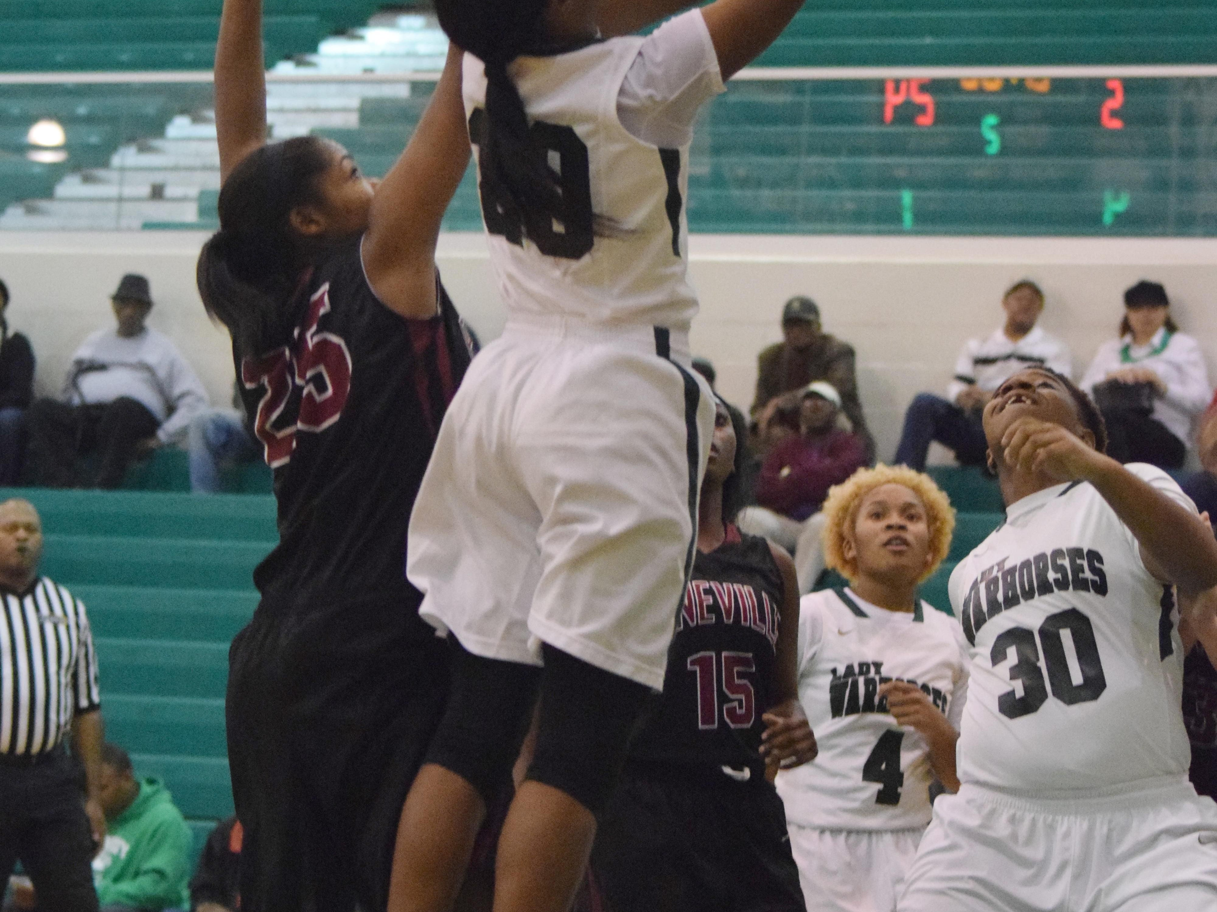 Peabody's Azia Reed (20, right) goes for two as Pineville's Krystal Freeman (25, left) blocks Tuesday.